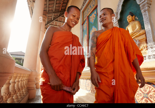 Two buddhist monks meeting and saluting in a temple, Phnom, Penh, Cambodia, Asia. Dolly shot - Stock-Bilder