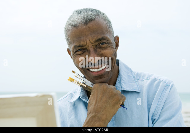 Senior man holding paint brushes outdoors, smiling at camera, canvas in foreground - Stock Image