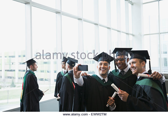 College graduates cap and gown taking selfie - Stock Image
