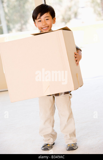 Young boy with box in new home smiling - Stock Image