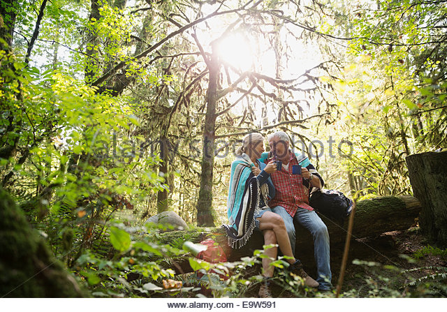 Couple wrapped in blanket relaxing in woods - Stock Image