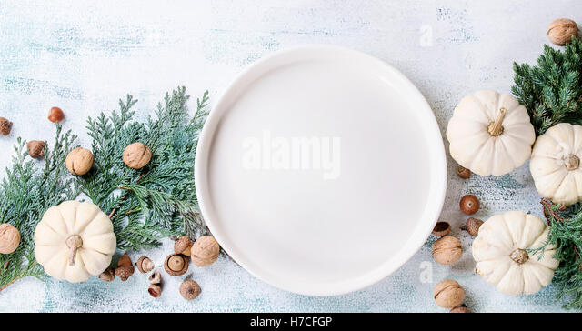 Holiday table decoration with white decorative pumpkins, thuja branches, walnuts, acorns and empty dinner plate - Stock Image
