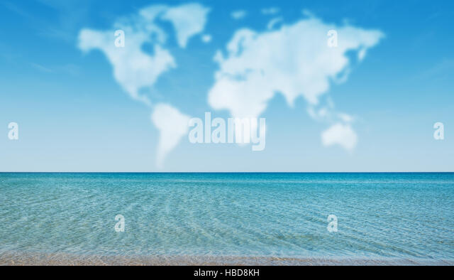 Clouds in shape of world map above ocean at sunny day - Stock Image
