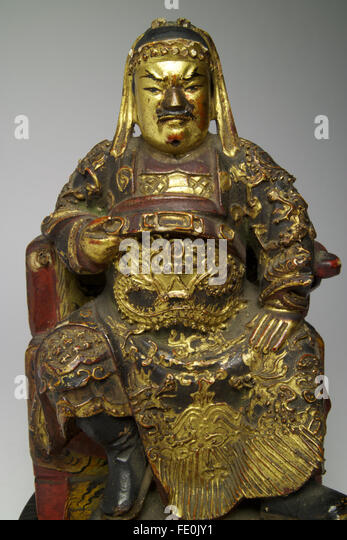 Antique Chinese polychrome lacquered wood figure of Guandi shown seated with one hand raised up and clasping the - Stock Image