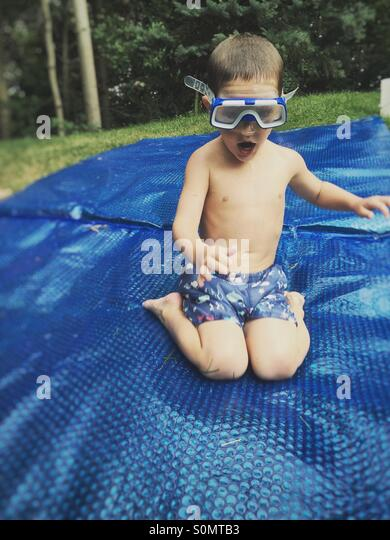 Funny image of a young boy wearing a diving mask while sliding on a wet sheet of plastic - Stock Image