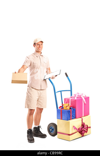 Full length portrait of a delivery person posing next to a hand truck with presents - Stock Image