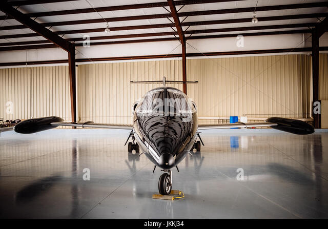A black 1970's vintage Lear Jet, parked in an airport hanger, ready for flight. - Stock Image