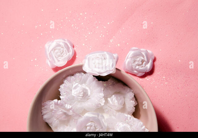 Bowl with glitter white flower on a pink background - Stock Image
