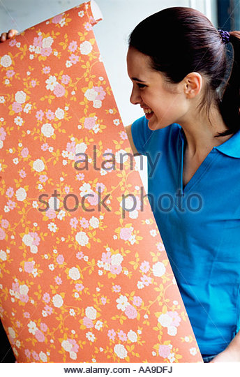 Woman unrolling wallpaper - Stock Image