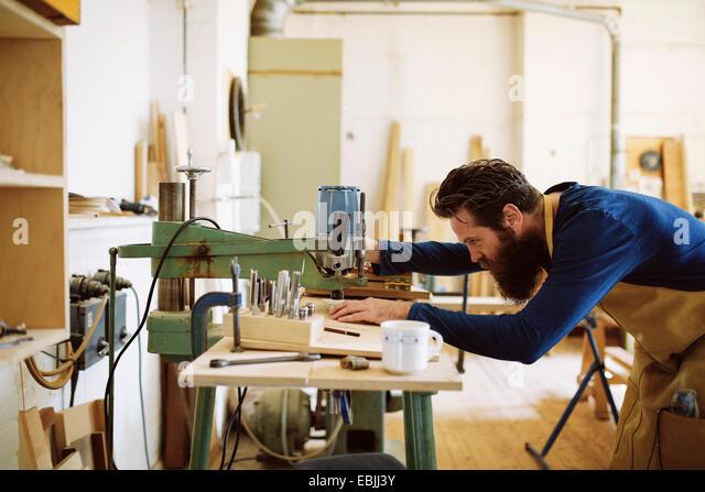 Mid adult craftsman using machine in pipe organ workshop - Stock Image