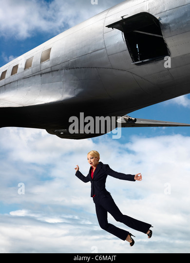 humorous image of woman falling from open hatch of airplane in flight - Stock Image