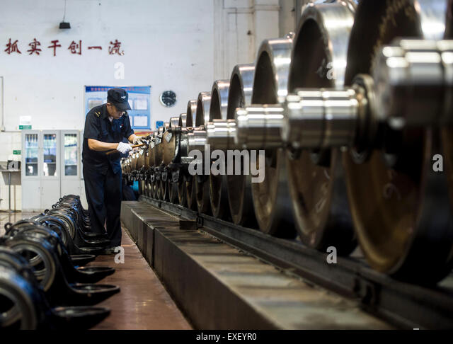 Wuhan, China's Hubei Province. 13th July, 2015. A worker inspects wheels at a train wheels service center in - Stock Image