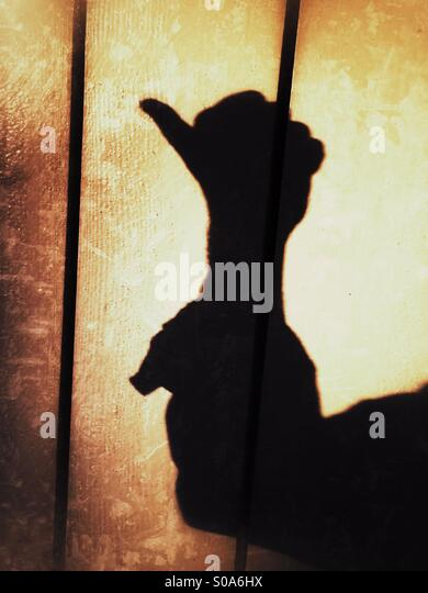 A man casting a shadow on a wall, counting on his hand. Number one. - Stock Image