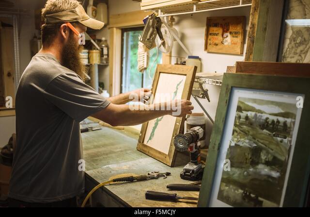 Artist working in workshop, framing artwork - Stock Image