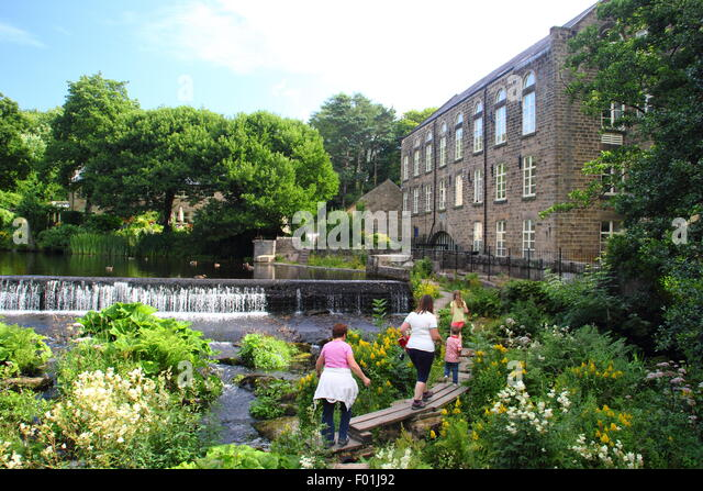 People walk over the wooden public footbridge by Bamford Mill and weir in the Peak District Derbyshire England UK - Stock Image