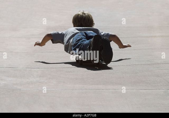 A young boy joyfully rides on a skateboard during summer break. - Stock Image