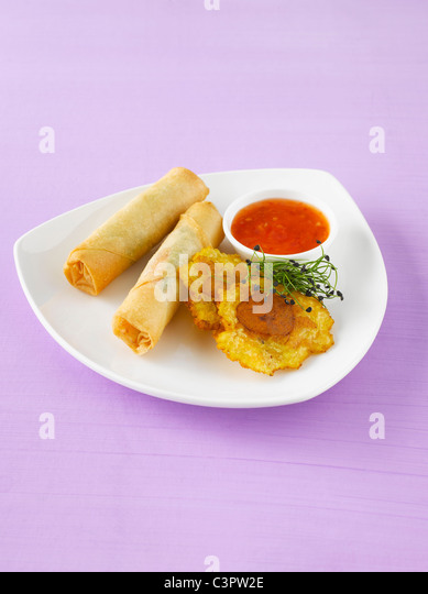 Spring rolls and plantain crisps with chili sauce - Stock-Bilder