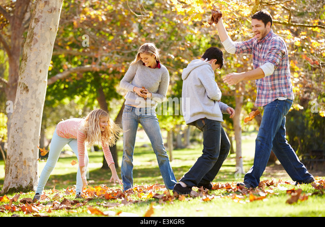 Family Throwing Autumn Leaves In The Air - Stock-Bilder
