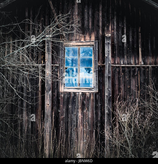 Old and abandoned mill with wooden wall and window - Stock Image