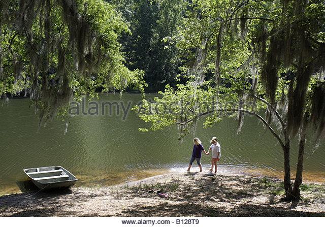 Alabama Greenville Sherling Lake Park teen girl grandmother woman wading barefoot Spanish moss - Stock Image