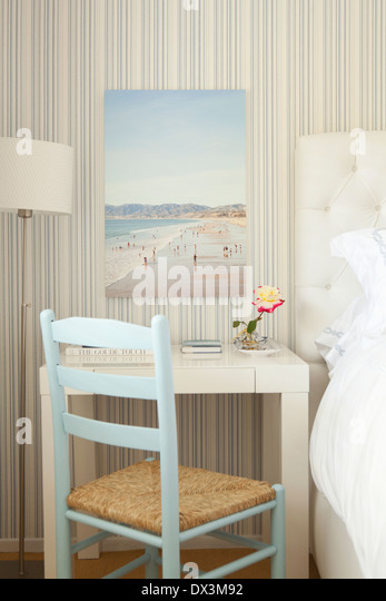 Beach painting above writing desk in blue and white bedroom - Stock-Bilder