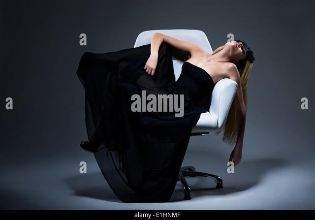 Harmony & Sensuality. Romantic Blond Female in Black Dress resting in Armchair. Satisfaction - Stock Image