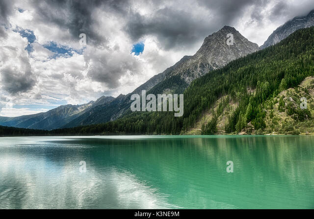 Lake of Anterselva surrounded by mountains with blue sky and dark clouds in the background on a summer day, Sud - Stock Image