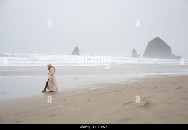 Woman talks on phone with Haystack Rock in the distance at popular tourist destination, Cannon Beach, Oregon, USA - Stock-Bilder
