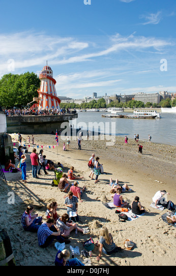 People enjoying themselves on the foreshore of the River Thames. - Stock Image