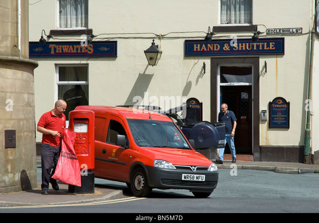 Postman emptying post-box in front of Hand & Shuttle pub, Padiham, Lancashire, England UK - Stock Image
