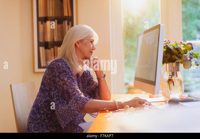 Senior woman working at computer in home office - Stock-Bilder
