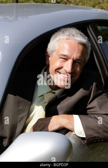 Mature handsome man sitting in car smiling - Stock Image