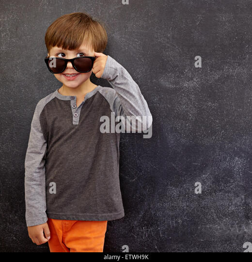 Portrait of a little boy in sunglasses looking at away at copy space. Cool boy peering over his sunglasses against - Stock Image