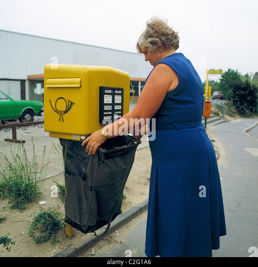 Eighties, people, communication, letter mail, postal employee, woman clears a letter-box with a mailbag, aged 40 - Stock Image