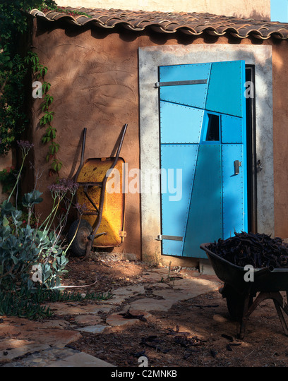 Yellow wheelbarrow outside quirky blue patchwork shed door - Stock Image