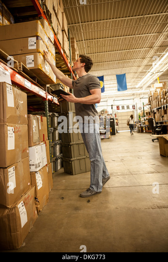 Worker in warehouse selecting items from cardboard boxes - Stock Image