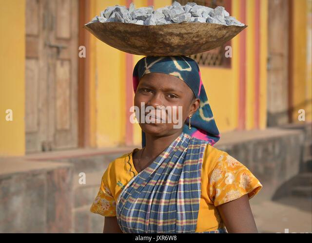 Closeup street portrait of a sari-clad young Indian Adivasi tribal woman, balancing on her head a metal bowl with - Stock Image