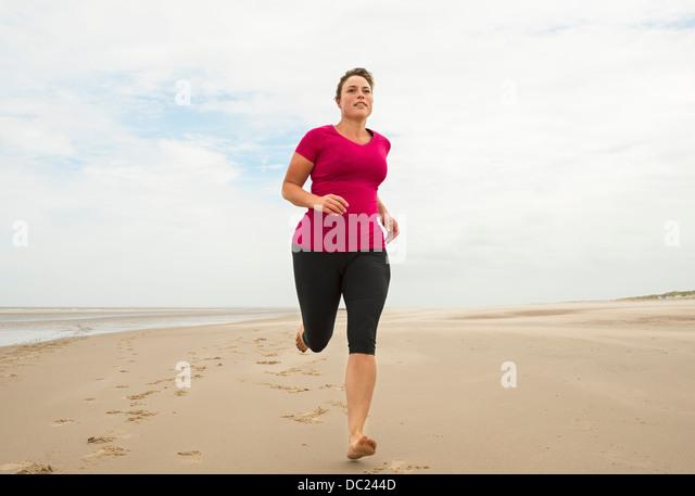 Woman running on beach - Stock-Bilder