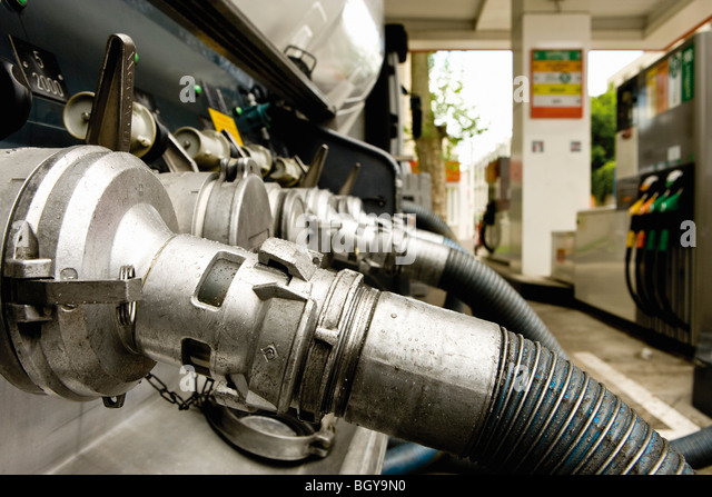 Hoses connected to fuel tanker outlets transferring fuel to gas station storage tanks - Stock Image