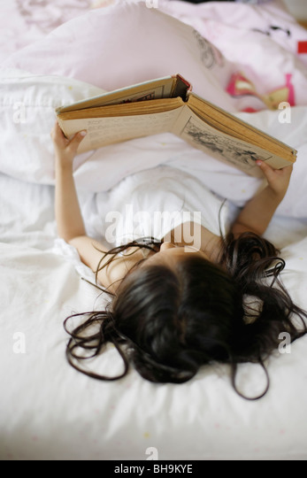 Six year old girl reads book - Stock Image