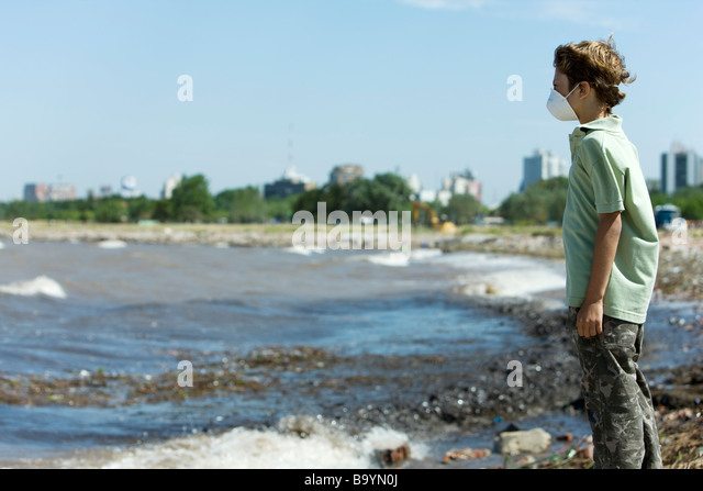 Boy wearing pollution mask, standing on polluted shore - Stock Image