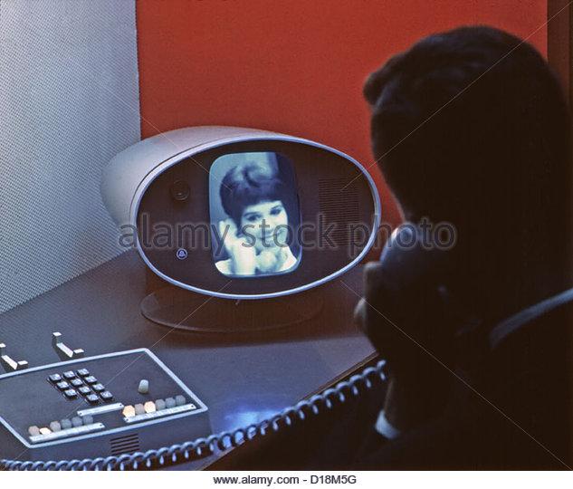 Visitors to New York's World's Fair speak on the Picturephone, Bell Telephone System Pavillion, Flushing - Stock-Bilder
