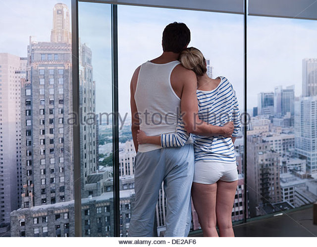 Couple hugging and looking outside - Stock-Bilder