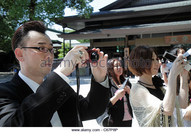 Japan Tokyo Shibuya-ku Meiji Jingu Shinto Shrine wedding reception Asian woman man taking pictures camera - Stock Image