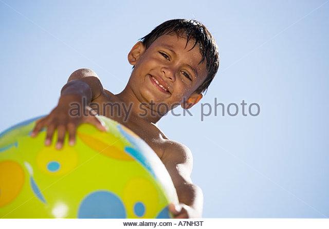 Boy 7 9 holding green beach ball smiling portrait upward view unusual angle - Stock Image