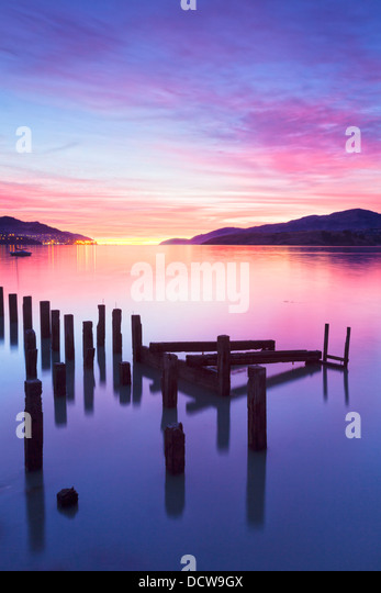 Beautiful sunrise with colours of pink, orange and purple, over Governors Bay, Canterbury New Zealand. In the foreground... - Stock Image