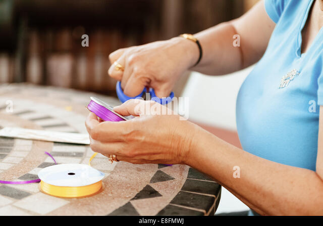 Close-up of woman cutting colorful ribbon - Stock Image