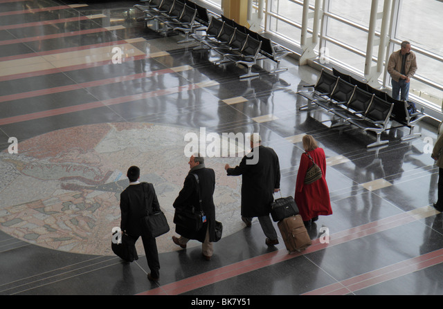 Virginia Arlington Ronald Reagan Washington National Airport DCA terminal man woman rolling luggage passenger commuter - Stock Image
