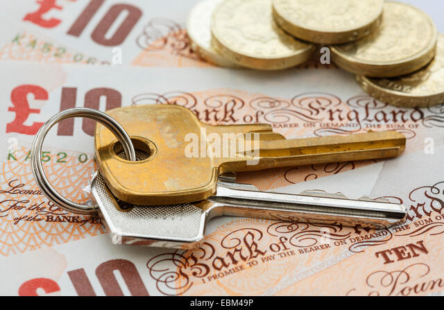 House keys on money sterling notes with pound coins to illustrate UK property mortgage prices concept. England, - Stock Image