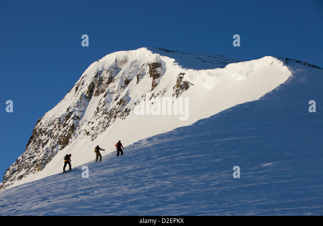 Three backcountry skiers hiking up a mountain in pink sunrise light. - Stock-Bilder